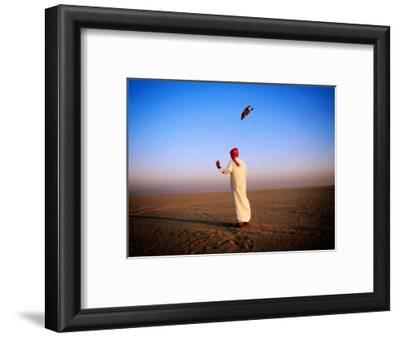 Arab Handler Swinging Lure During Hunting Falcon Training Exercise in Desert