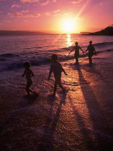 Family Walking on Beach at Dusk, HI by Mark Gibson