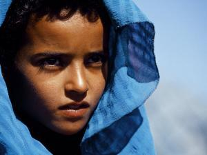 Young Girl in Characteristic Saharan Blue Headscarf Looking into Distance, Sahara, Southern Morocco by Mark Hannaford