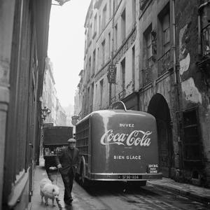 A Man Walks His Dog Beside a Bus with Coca Cola Advertisement, France, 1950 by Mark Kauffman