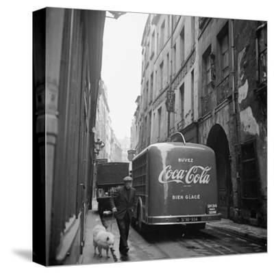 A Man Walks His Dog Beside a Bus with Coca Cola Advertisement, France, 1950
