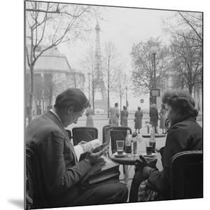 Parisian Couple Drinking Coca Cola at a Sidewalk Cafe While Reading, Paris, France, 1950 by Mark Kauffman