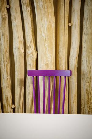 Pink chair infront of a timber background