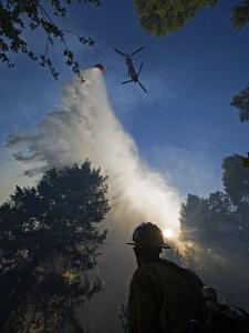 A helicopter makes water drops on a wildfire in Boise National Forest by Mark Thiessen
