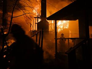 Firefighters spray down a burning house in Running Springs by Mark Thiessen