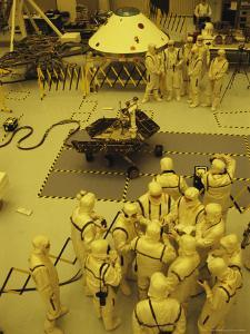 Journalists, Engineers and Technicians Examine a Robot in a Clean Room by Mark Thiessen