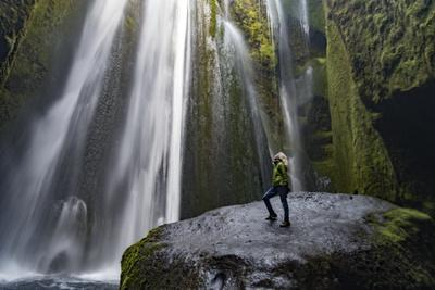 Iceland, Seljalandsfoss. Woman on large rock in front of streaming falls in green slot canyon. (MR)