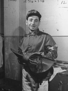 Jockey Johnny Longden Smiling and Holding Saddle by Martha Holmes