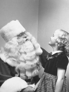 Santa Claus and 5 Year Old Demonstrating Right Way to Hold Child by Martha Holmes