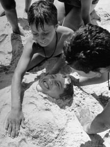 Settlement House Children Burying Boy under Sand at the Beach by Martha Holmes