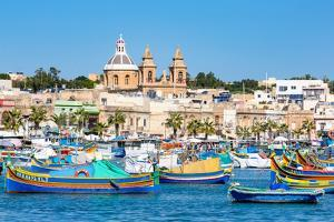 Traditional brightly painted fishing boats in the harbour at Marsaxlokk, Malta, Mediterranean, Euro by Martin Child