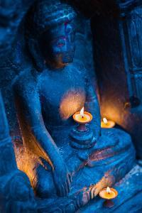 A stone Buddha statue holds a ceremonial candle. by Martin Edstrom