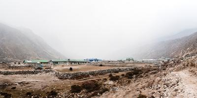 Fog covers a small village in the Himalaya mountains, with yaks grazing by Martin Edstrom