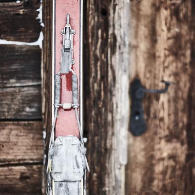 old red skis in front of old wooden door