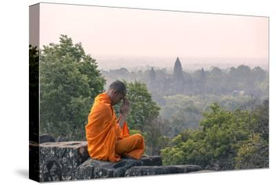 Cambodia, Siem Reap, Angkor Wat Complex. Monk Meditating with Angor Wat Temple in the Background
