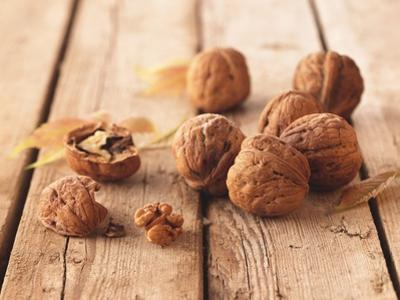 Walnuts on a Wooden Background by Matthias Hoffmann