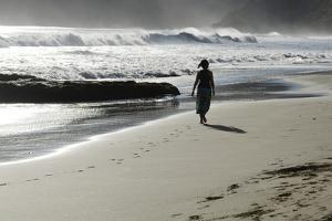 A Woman Walks Along the Beach as the Surf Rolls In by Mauricio Handler