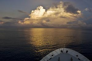 Clouds Gather over a Calm Sea as Seen from the Bow of an Expedition Ship, the Hanse Explorer by Mauricio Handler