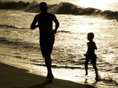 Father and Son Run on Grande Riviere Beach at Sunset by Mauricio Handler
