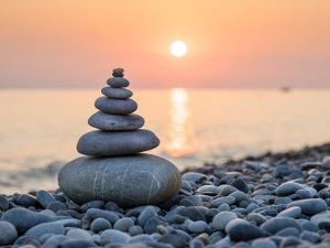 Pyramid of Stones for Meditation Lying on Sea Coast at Sunset by Maxim Blinkov