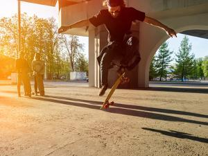 Silhouette Skateboarder Jumping in City on Skateboard under the Bridge. in the Background Two Young by Maxim Blinkov