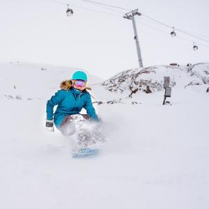 Young Woman Snowboarder in Motion on Snowboard in Mountains by Maxim Blinkov