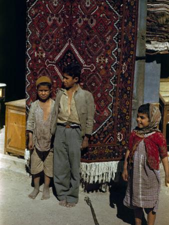 Children Stand Beside Persian Rug Hanging at a Storefront's Entrance