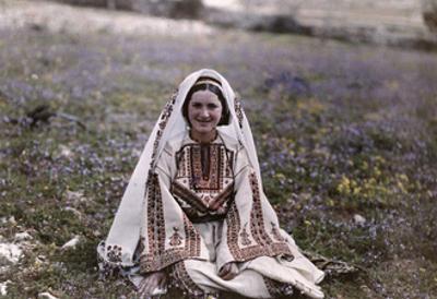 Christian Girl Wearing a Festal Costume Sits in a Field in Ramallah