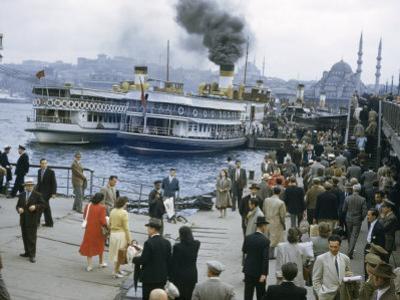 People Bustle Along Dock Near Steamers Emitting Smoke