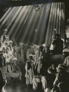 Rays of Sunlight Shine on Men and Boys in a Crowded Warehouse by Maynard Owen Williams