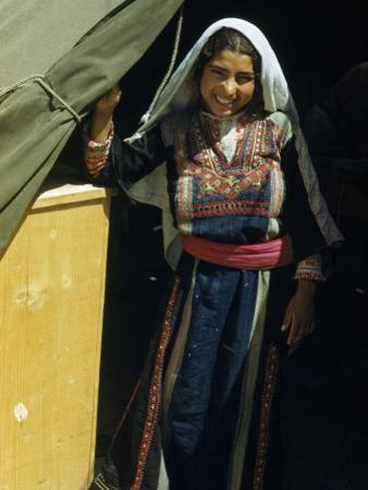Smiling Refugee Stands at a Tent's Entrance in a Refugee Camp