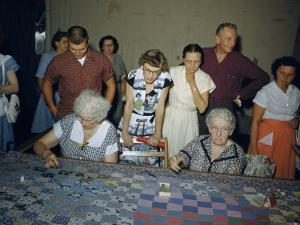 Women Demonstrate How to Make a Patchwork Quilt at a Festival by Maynard Owen Williams