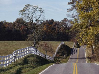 A White Wood Fence Follows a Winding Country Road