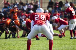 American Football Game with out of Focus Players in the Background by melis