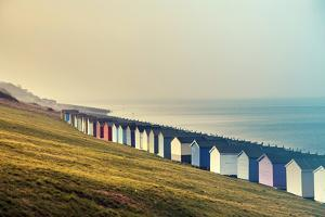 Row of Colored Beach Huts with Stormy Blue Sky on the Beach of Tankerton near Whitstable in Kent, U by melis