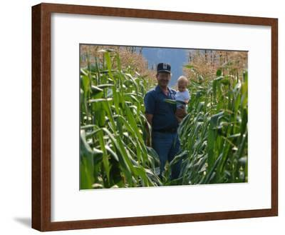 A Farmer Stands with His Child in a Cornfield