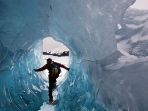A hiker explores an ice cave recently revealed at Mendenhall Glacier by Melissa Farlow