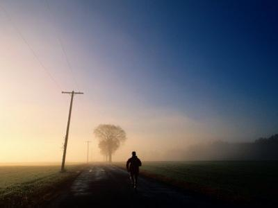 A Lone Jogger Runs Down a Rural Road in Early Morning Fog