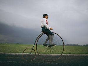 A Man Pedals an Old-Fashioned Bicycle Ahead of an Indiana Thunderstorm by Melissa Farlow