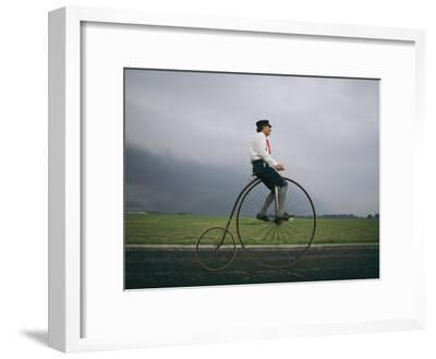 A Man Pedals an Old-Fashioned Bicycle Ahead of an Indiana Thunderstorm