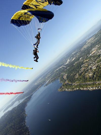 Members of US Navy Parachute Team, the Leap Frogs, Perform Bi-Plane with Parachutes Above Seattle--Photographic Print