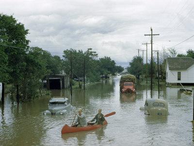 https://imgc.artprintimages.com/img/print/men-paddle-canoe-down-street-submerged-by-flash-flood-in-may-1951_u-l-p8jcnk0.jpg?p=0