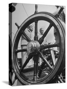 Men Standing at Attention on the Quarter Deck of a Sailing Ship as Viewed Through the Ship's Wheel