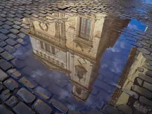 Cuba, Havana, Havana Vieja, reflection of historic building in puddle on cobblestone street. by Merrill Images