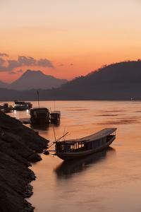 Laos, Luang Prabang, boats on Mekong River at sunset. by Merrill Images