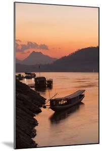 Laos, Luang Prabang, boats on Mekong River at sunset. by Merrill Images
