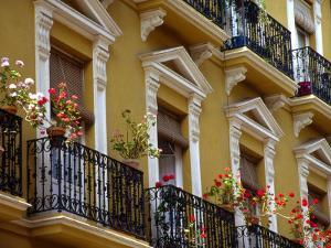 Spain, Sevilla, Andalucia Geraniums hang over iron balconies of traditional houses by Merrill Images