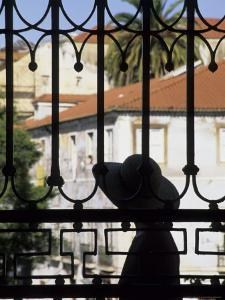 Tourist Gazes at Historic House through Iron Grillwork of Church, Lisbon, Portugal by Merrill Images
