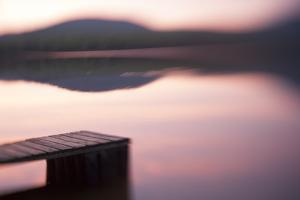 Usa, New Hampshire, Lyme. Dock and reflection of mountain in Hinman Pond at sunset. by Merrill Images