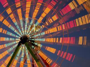 USA, Washington State, Puyallup, ferris wheel in motion at annual Puyallup Fair at night. by Merrill Images